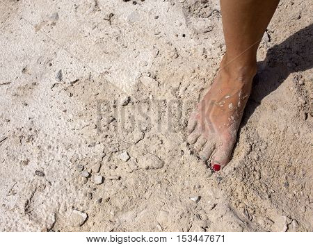 Woman foot standing on a dry beach sand.