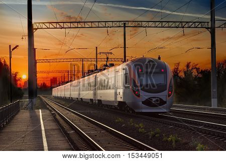 Leaving high-speed inter-city train in the city on the sunset background