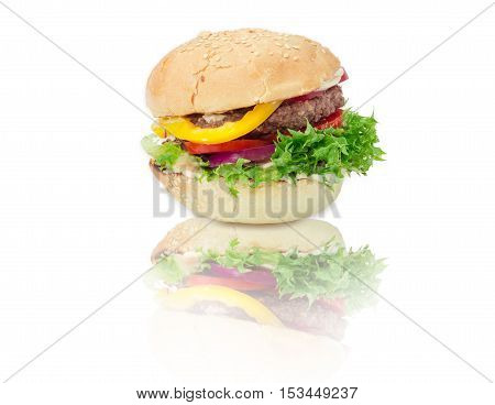 Traditional hamburger with beef patty vegetables and condiments on a reflective surface on a light background