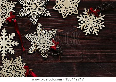 Christmas soft beige wooden snowflakes on a vintage wood brown background. New Year frame background.