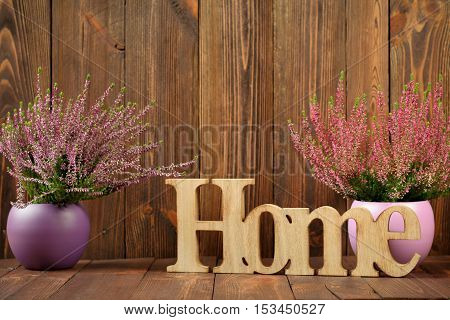 Heathers in ceramic pots and the letter 'home' against dark wooden planks