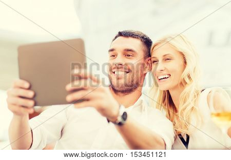 love, dating, people, technology and holidays concept - happy couple with tablet pc computer and glasses of wine at restaurant lounge or terrace