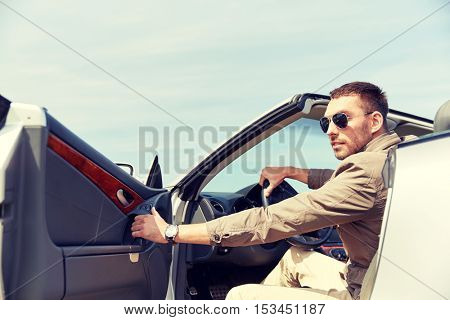 road trip, travel, transport, leisure and people concept - happy man opening door of cabriolet car outdoors