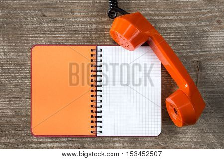 Orange telephone receiver and blank notebook for copy-space