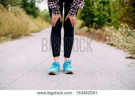 Female Feet In Sneakers.  Sportswoman Tying Her Shoelaces Before