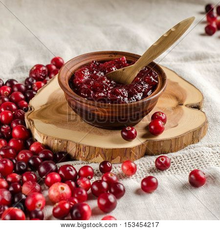 Fresh cranberries. The red berries. Jam from cranberries in a bowl with a spoon. Light linen tablecloth.