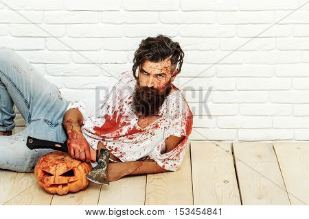 Bearded zombie man with beard vampire or bloody war soldier with wounds and red blood with halloween pumpkin and axe lies on wooden floor