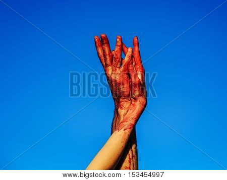 zombie hands female of war soldier with bloody wounds and red blood on skin on blue sky background