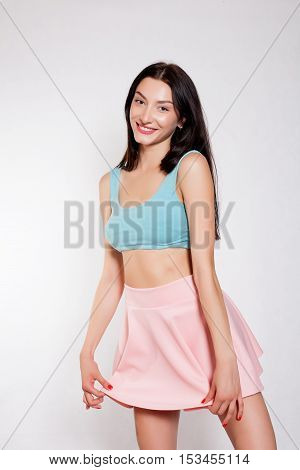 Sexy glamorous girl in pink skirt and turquoise top. brunette with bright makeup. Young beautiful woman in studio. Girl standing in candid provocative pose. Isolated.