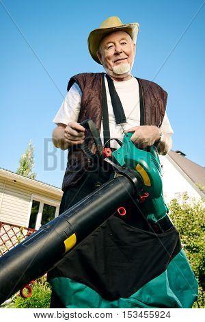 Autumn in a garden. Senior man removes fallen leaves in his garden using leaf blower.