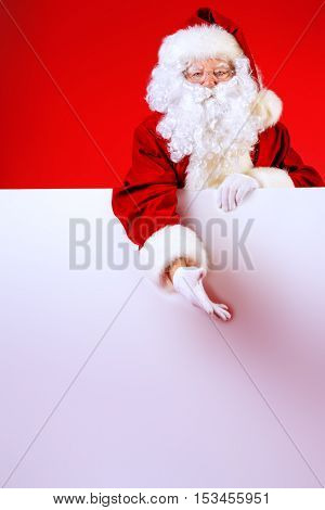 Santa Claus holding white billboard over red background. Copy space. Christmas.