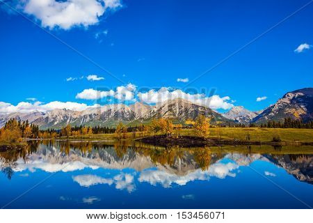 Bright shining autumn day in Canmore. Majestic mountains and scenic cumulus clouds are reflected in  smooth water of the lake. The concept of recreational tourism