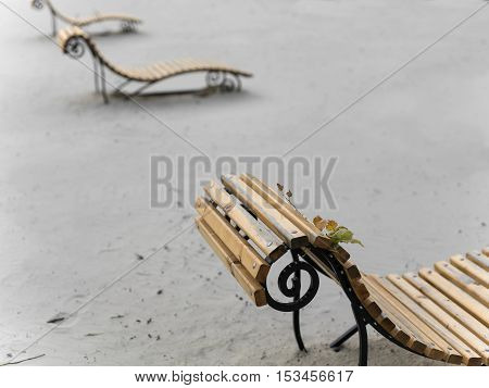 Abandoned beach with a row of benches concept of the end of tourist season. Outdoor shot focus in the foreground