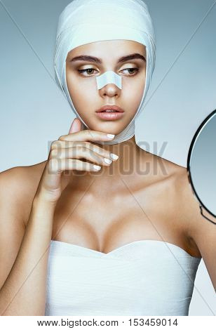 Beautiful Woman after plastic surgery looking in mirror. Photo of woman wrapped in medical bandages. Beauty concept