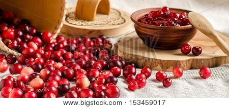 Red cranberries. Jam from cranberries in a bowl. Birch bark basket. A wooden stand. Light linen tablecloth. A rustic style.