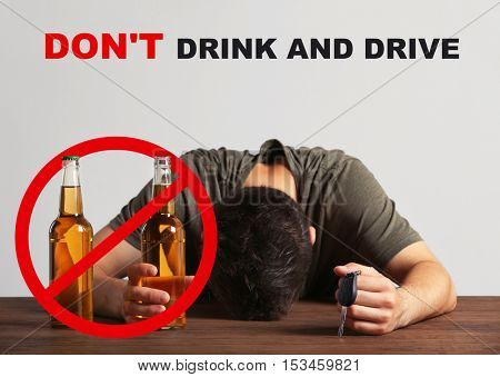 Drunk young man with car key and beer bottle at bar. Text DON'T DRINK AND DRIVE on background.