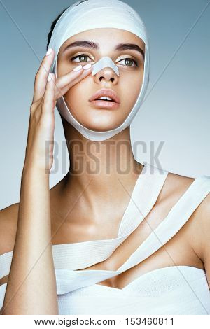 Woman removes the bandages from her head and touching her new face. Portrait of young models face in medical bandage after beauty surgery. Plastic Surgery concept