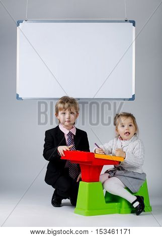 photo of young boy teaching younger sister
