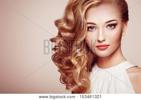 Fashion portrait of young beautiful woman with jewelry and elegant hairstyle. Blonde girl with long wavy hair. Perfect make-up. Beauty style woman with diamond accessories