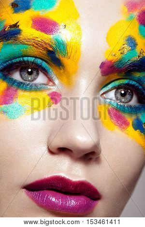 Beautiful woman face. Beauty girl face with colorful makeup. Beauty fashion. Eyelashes. Red lipstick. Cosmetic Eyeshadow. Make-up detail. Rainbow Colors