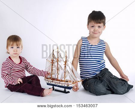 boy and girl playing with ship on white