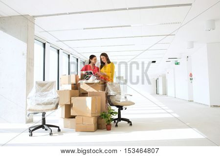 Businesswomen unpacking cardboard boxes in new office