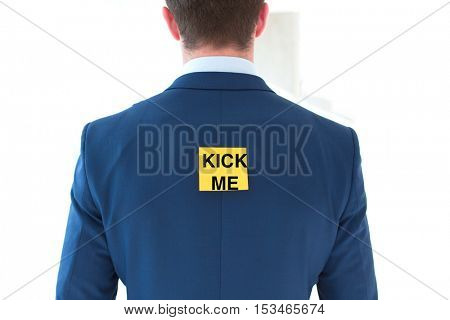 Rear view of young businessman with Kick Me sticky note at office