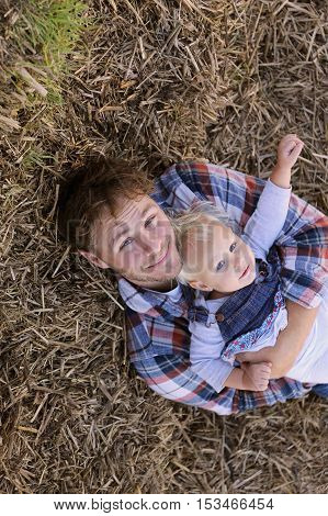 A happy young father is relaxing on the farm on a bale of hay while holding his 1 year old baby girl.