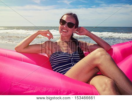 A pretty woman demonstrating her sincere smile, wearing brown sunglasses and blue and white striped swimming suit with the hands near her face reclining on a rosy airbed on a sunny day