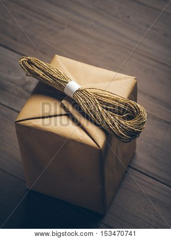 brown cube box with a bundle of string on, isolated on wooden table.