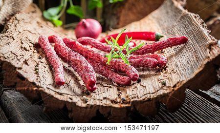 Closeup Of Fresh Thin Sausages On Bark