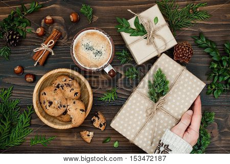 Opening Christmas present. Woman's hands holding decorated gift box on rustic wooden table. Ideal Christmas morning breakfast. Overhead flat lay top view