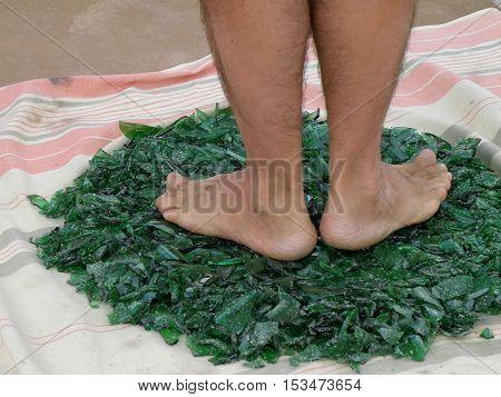 Human bare feet standing on the broken glass.