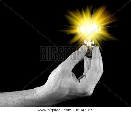 Hand holding isoliert auf schwarz Glühbirne