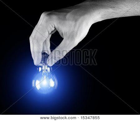 Hand holding light bulb isolated on black