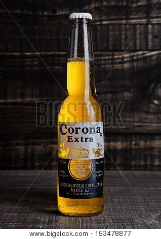 LONDON UNITED KINGDOM - October 23 2016: Bottle of Corona Extra Beer on wooden background. Corona produced by Grupo Modelo with Anheuser Busch InBev is the most popular imported beer in the US.