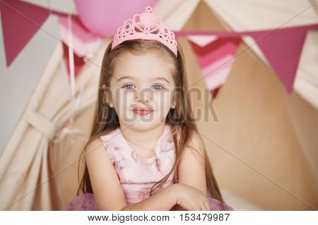 Closeup funny little princess girl in pink crown and dress posing on tent background. Preschooler close up portrait with copy space