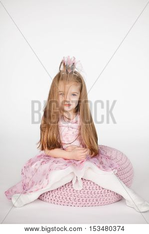 Beautiful girl looking sad and tired with messy hair. Vertical portrait of cute kid with blond long hair isolated on white background