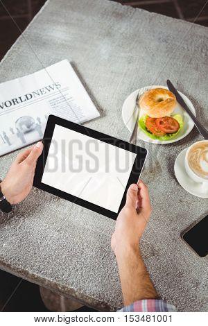 Hands of man holding digital tablet in cafeteria