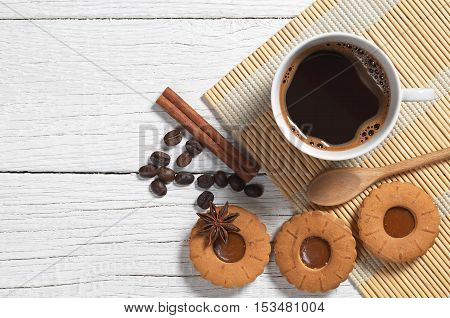 Cup of hot coffee and cookies rings with caramel on white wooden background top view. Space for text