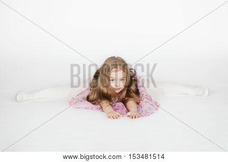 Little preschoolder girl sitting on the splits. Kid girl on the twine isolated on white background.