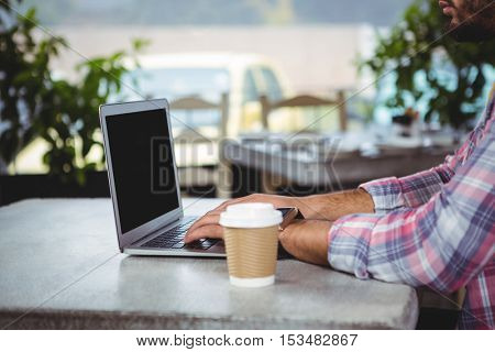 Mid-section of man using laptop in cafeteria