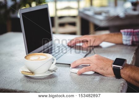 Hands of man using laptop in cafeteria