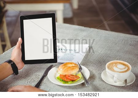 Hand of man holding digital tablet in cafeteria