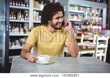Man talking on mobile phone in cafeteria