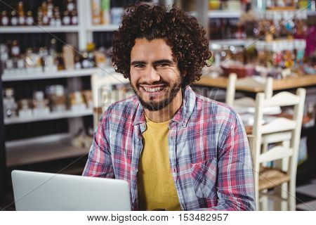 Portrait of man smiling while using laptop in cafeteria