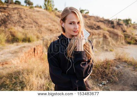 Young fitness runner woman resting on beach listening to music with earphones