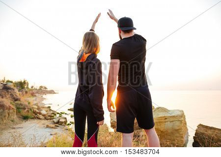 Back view of a young sports couple standing on a hill and greeting sunset