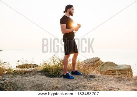 Young sporty bearded man athlete resting after jogging at the beach and holding water bottle