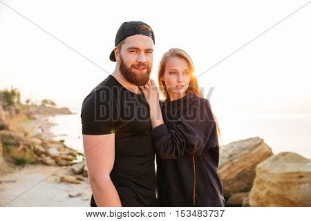 Beautiful sports couple standing together at the seaside during sunset